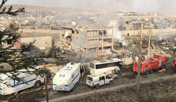 Turkish police and firefighters seen near a damaged police headquarters after a car bomb killed Turkish police officers and wounded scores more on August 26, 2016 in southeastern Turkey.