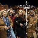 Women of the Wall chair Anat Hoffman, holding onto MK Ksenia Svetlova (center), who is helping carry a Hanukkah menorah to the women's section at the Kotel.
