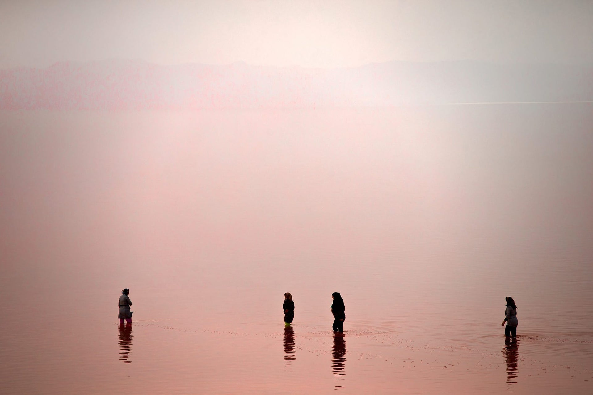 This picture taken on Thursday, Aug. 25, 2016, shows Iranians spending time in Urmia Lake near Urmia, North-western Iran. Hopes for survival of Urmia salt lake have been revived after more rains boosted a government program aimed at preserving the almost dried up water body.