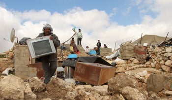 A Palestinian man collects items from his home after it was demolished by Israeli bulldozers in the Hebron Hills in the West Bank, February 2016.