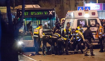 Paramedics remove the body of a terrorist from the scene of an attack on a Jerusalem street, December 6, 2015. Traffic is at a standstill.