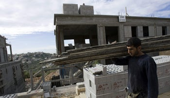 A Palestinian laborer works at a construction site in the Israeli settlement of Beit Arye in the West Bank, 2009.