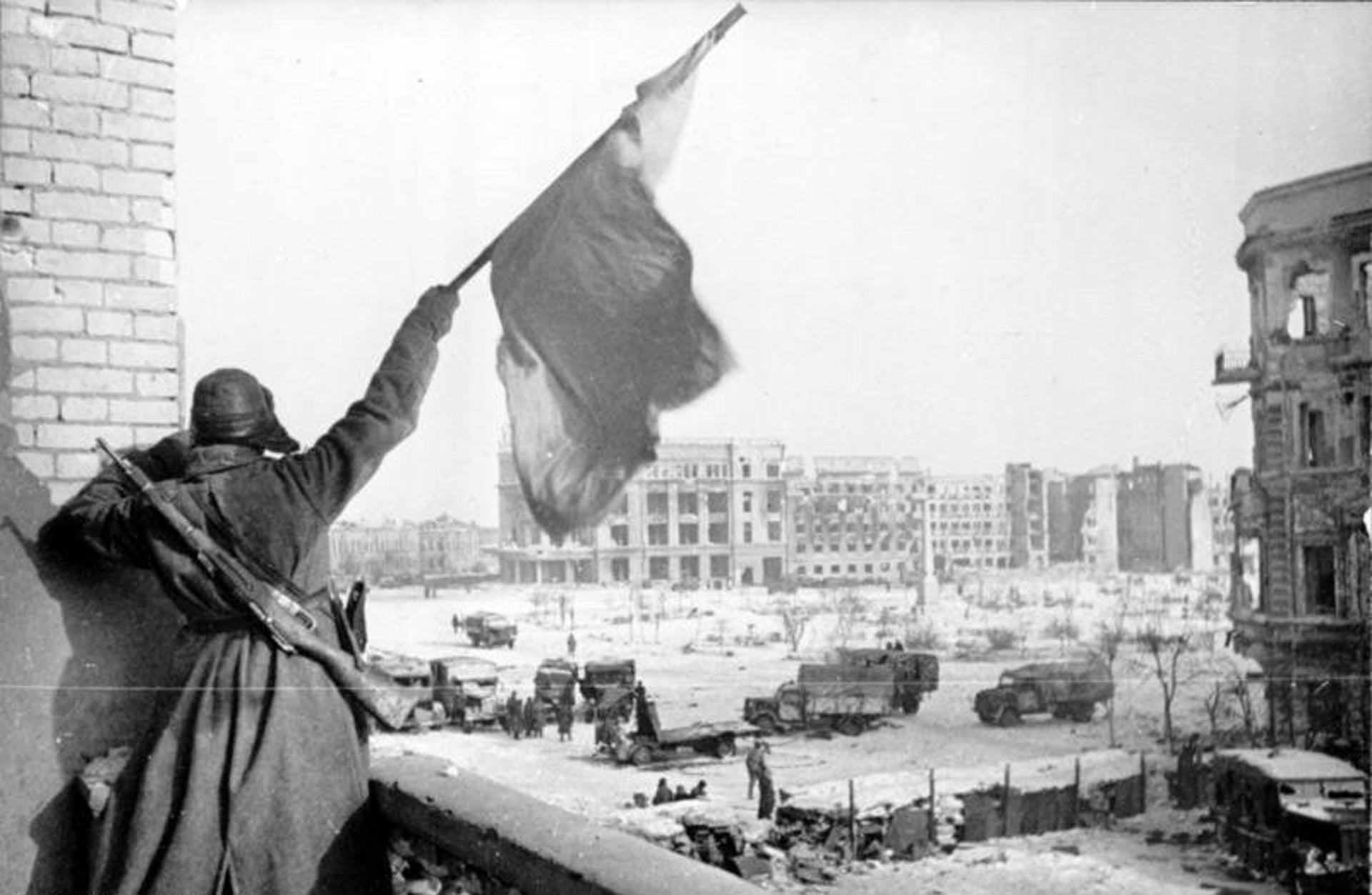 A Soviet soldier waving the Red Banner over the central plaza of Stalingrad in 1943.