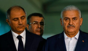 Turkey's Prime Minister Binali Yildirim speaks to the press next to Interior Minister Efkan Ala at Ataturk airport in Istanbul, Turkey, June 29, 2016.