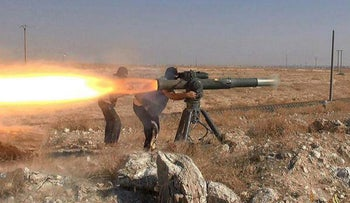 In this file photo released on June 26, 2015, by supporters of the Islamic State militant group on an anonymous photo sharing website, Islamic State militants fire an anti-tank missile in Hassakeh, northeast Syria.
