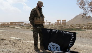 A member of the Syrian pro-government forces carries an Islamic State (ISIS) group flag as he stands on a street in the ancient city of Palmyra on March 27, 2016.