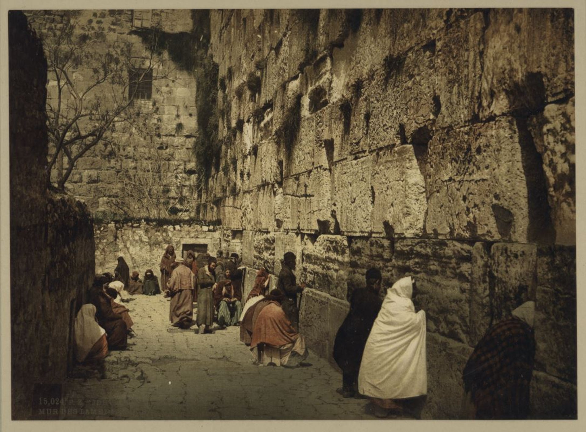 The Western Wall at the end of the 19th century. Men and women are seen leaning on the wall.
