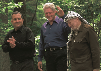 U.S. President Bill Clinton walks with Israeli Prime Minister Ehud Barak (L) and Palestinian President Yasser Arafat (R) on the grounds of Camp David during peace talks, July 11.