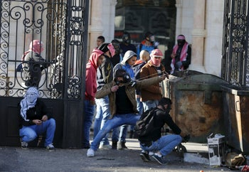Palestinian protester uses a slingshot to hurl stones towards Israeli troops during clashes in the West Bank city of Bethlehem December 4, 2015.