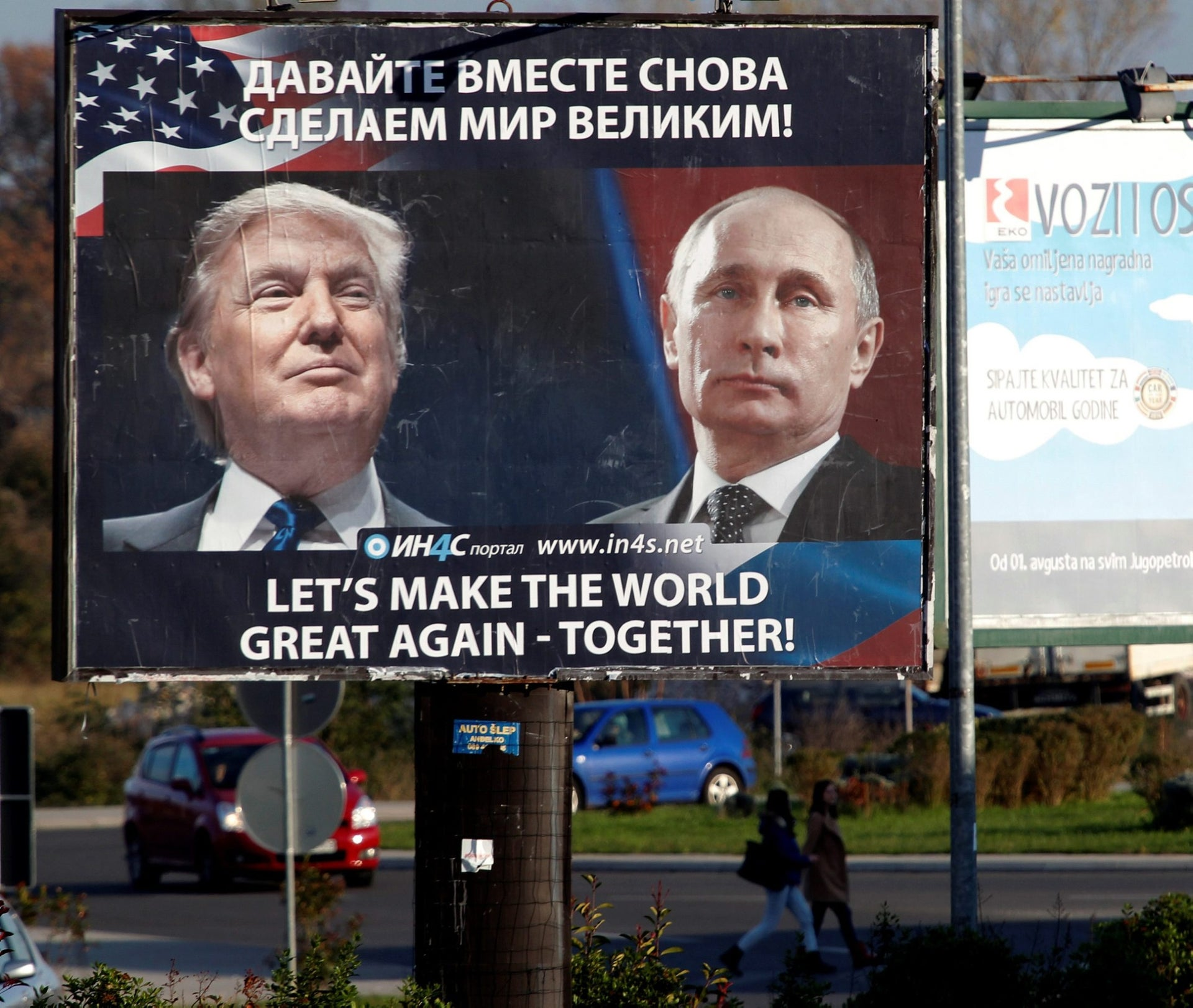 Pedestrians cross the street behind a billboard showing a pictures of U.S. President-elect Donald Trump and Russian President Vladimir Putin in Danilovgrad, Montenegro, November 16. 2016.