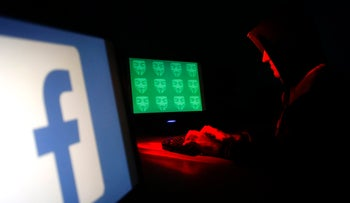 Man poses in front of on a display showing a Facebook logo and the word 'cyber' in binary code, in this picture illustration. Facebook, Google and Twitter are stepping up efforts to combat online propaganda and recruiting by Islamic militants, December 27, 2014.