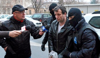 Marcel Lazar Lehel is escorted by masked policemen in Bucharest, after being arrested in Arad, 550 km (337 miles) west of Bucharest January 22, 2014.