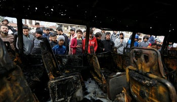 People look at a burned vehicle at the site of car bomb attack in Baghdad's Sadr City district, in Iraq, January 2, 2017.