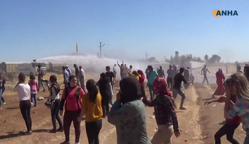 Screenshot from ANHA footage of Turkish authorities firing water cannons on protesters at the Syrian border.
