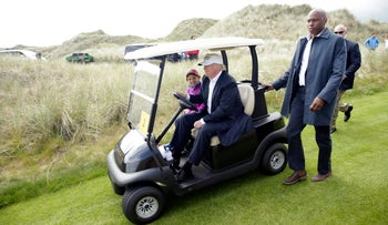 Donald Trump driving a golf cart at a course he owns in Aberdeen, Scotland, in June.
