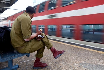 FILE PHOTO: Israeli soldiers wait at Tel Aviv train station.