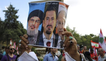 A Lebanese man holding a poster featuring Hezbollah leader Hassan Nasrallah (left), Prime Minister Saad Hariri and President Michel Aoun.