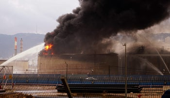 Firefighters work to extinguish a fuel tank on fire at Oil Refineries Ltd. in Haifa, December 25, 2016.
