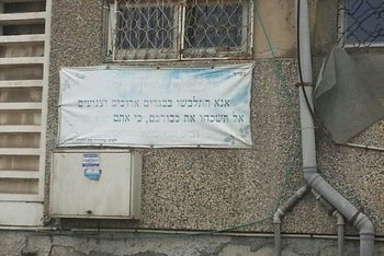 """A sign in an Ashdod neighborhood asks passersby to """"Please wear long and modest clothing."""""""
