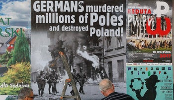 A workers puts up a poster in Warsaw, Poland, calling on Germany to pay reparations for World War II to Poland, August 24, 2017.