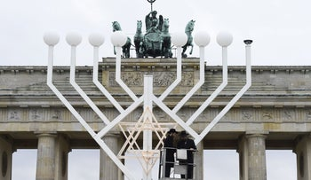 Two rabbis stand on a elevated platform as a giant eight- branched candelabrum Menorah is installed in front of the Brandenburg Gate, Berlin, December 4, 2015.