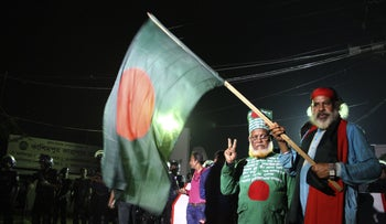 Bangladeshi activists who fought in the 1971 war wave a national flag as they gather near Kashimpur Central Jail on the outskirts of Dhaka on September 3, 2016.