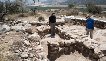 Archaeologists standing at a Hirbet Kaifeh.