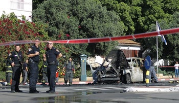 Police officers at the scene of the crime, with a burnt car next to them.