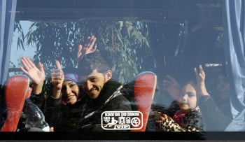 Syrians on a bus wave to the camera as hundreds of civilians and Syrian rebel forces began evacuating the last opposition-held district under a deal with the Syrian regime, Homs, Syria, December 9, 2015.