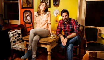 Sharon Horgan is sitting on a table next to and Rob Delaney, who is sitting on a chair, as they pose for a publicity shot for 'Catastrophe.'