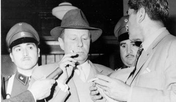 Nazi war criminal Walter Rauff, under police guard, surrounded by newsmen after he testified in the Supreme Court, Chile, in December 1962.