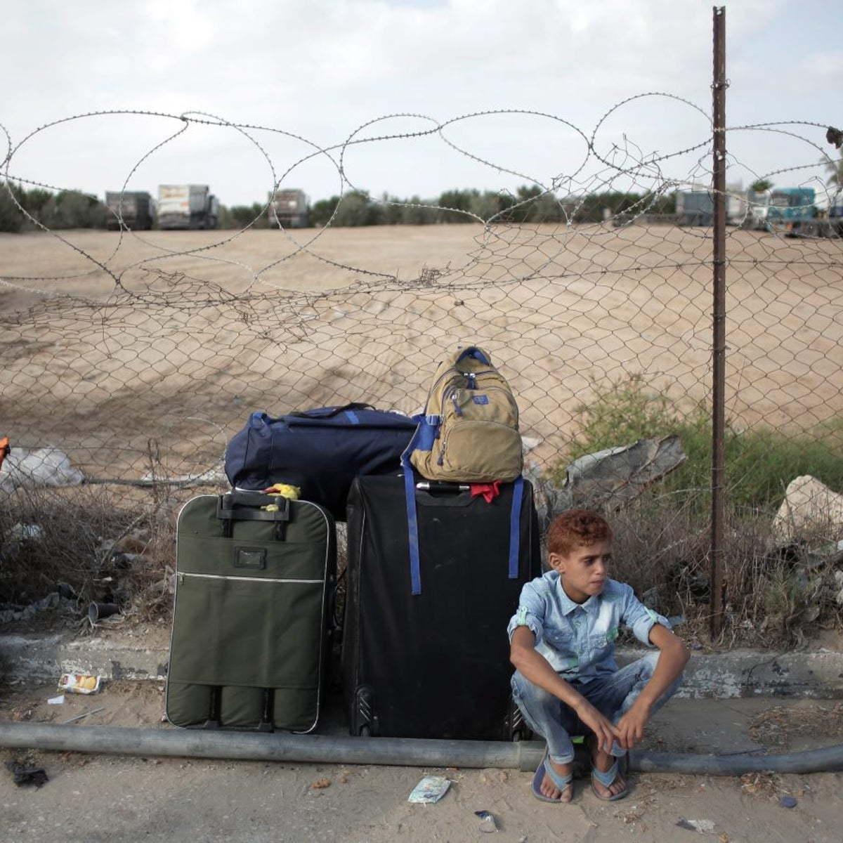A Palestinian boy sits next to the luggage as he and his family wait to cross the border into Egypt, at the Rafah crossing border in the southern Gaza Strip, Saturday, Sept. 3, 2016.