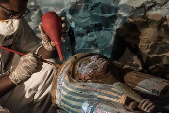 A picture taken on September 9, 2017 shows Egyptian archaeologist restoring a wooden sacrophagus at a newly-uncovered ancient tomb for a goldsmith dedicated to the ancient Egyptian god Amun, in the Draa Abul Naga necropolis on the west bank of the ancient city of Luxor, which boasts ancient Egyptian temples and burial grounds.