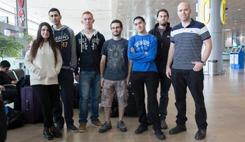 A group of young people (Yael Cohen, Tal Saar, Tomer Fidel, Yoav Sochen, Ido Brosh, Or Golan, and Neta Corem) stand at the airport, posing for the camera.