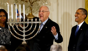 Rivlin lights a menorah as he joins Obama for a Hanukkah reception at the White House