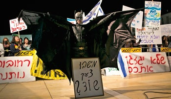 A protest against the gas deal is held in Tel Aviv, December 5, 2015. A protester dressed as batman spreads his wings. In front of him a sign says 'did anyone shout robbery?'