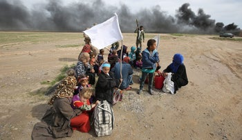 Displaced Iraqi families gather as they flee a military operation by Iraqi security personnel aimed at retaking areas from ISIS, in the desert west of Samarra, Iraq, March 3, 2016.
