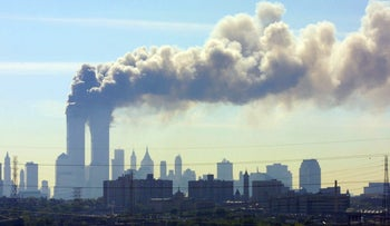 Smoke billows from the twin towers of the World Trade Center in New York as seen from the New Jersey Turnpike on Sept. 11, 2001