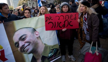 A supporter of Sgt. Elor Azaria, convicted of manslaughter in the deadly shooting of an incapacitated Palestinian attacker, holds a sign that reads 'Free Elor,' Tel Aviv, January 4, 2017.