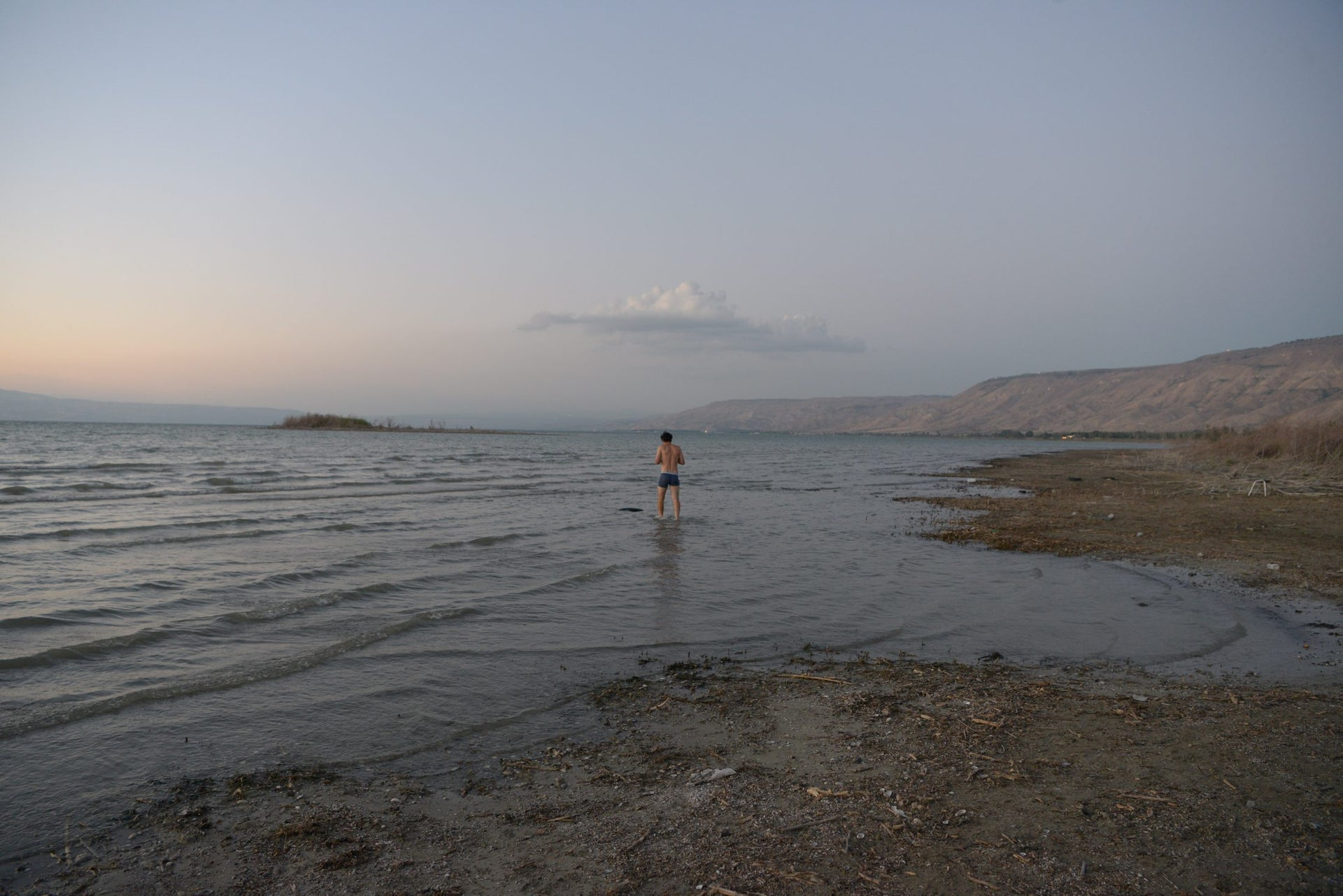 A bather in Lake Kinneret, September 2016. In the background is an island created as a result of the low water level.