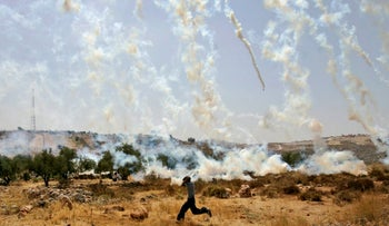 A Palestinian youth runs to avoid tear gas canisters fired by Israeli troops during a demonstration against Israel's separation barrier in the West Bank village Bilin, near Ramallah, Friday, June 6, 2008.