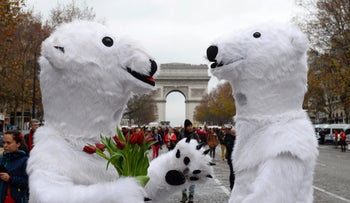 Activists dressed as polar bears are pictured as activists gather for a demonstration to form a giant red line at the Avenue de la Grande armee boulevard in Paris on December 12, 2015.