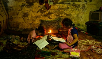 Palestinian children do their homeworks during a power cut in an impoverished area in Gaza City, on September 11, 2017