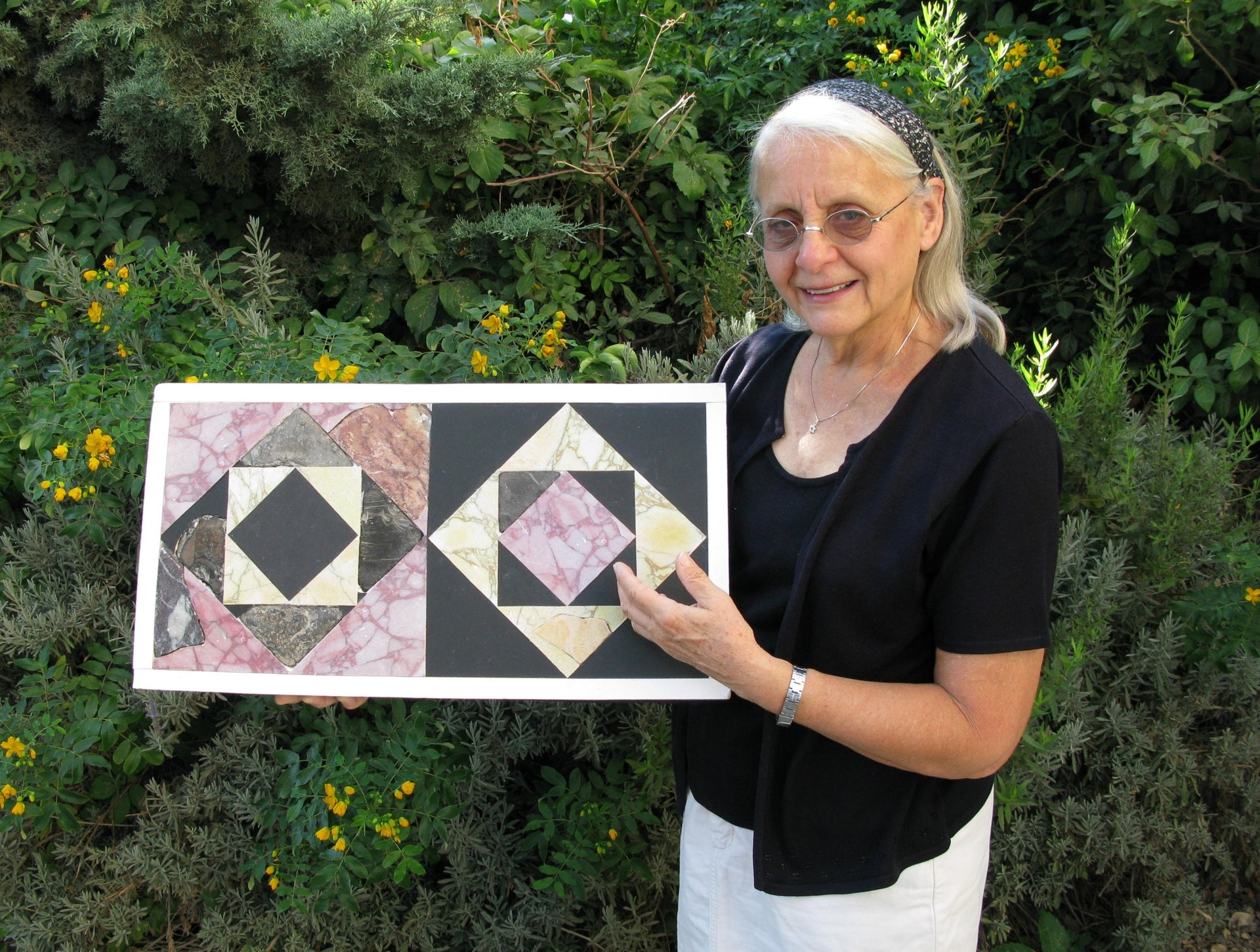 Frankie Snyder, shoulder-length smooth white hair, wearing glasses, black shirt and sweater, and white trousers, holding an example of two restored floor tiles from the courtyard of the Second Temple in Jerusalem.