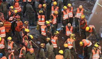 Rescue workers gather where a collapse took place at the construction site of a parking lot in the Ramat Hahayal neighborhood in Tel Aviv, Israel, September 5, 2016.