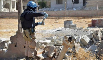 A UN researcher takes a sample of earth at a site targeted in the Damascus area, Syria, 2013.