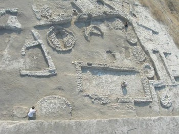 The oldest-known evidence of large-scale food storage: Bases of silos, Tel Tsaf. The picture is an aerial shot showing two archaeologists for scale, which shows how large the things actually were. They date to about 7,200 years ago and seem to have served mainly to store barley.