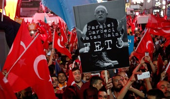 Erdogan supporters wave Turkish flags and hold a portrait of Gulen with Turkish words that read: 'the Coup nation traitor, FETO' in Ankara, Turkey, July 20, 2016.