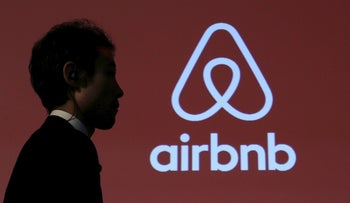 A man walks past a logo of Airbnb after a news conference in Tokyo, November 26, 2015.