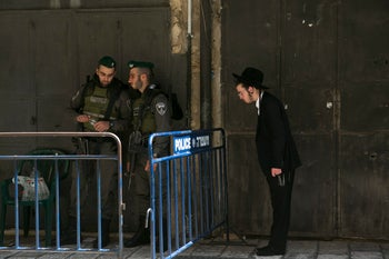 An ultra-Orthodox man prays at the entrance to the Temple Mount in the Old City of Jerusalem next to Israeli soldiers on September 1, 2017.